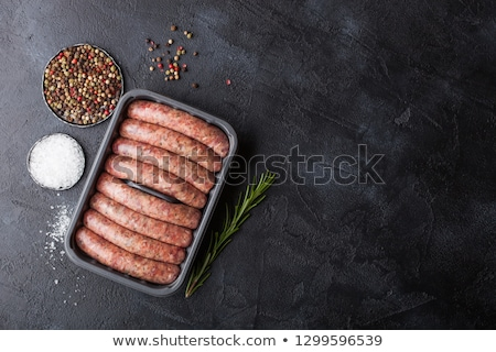 Raw beef and pork sausage in plastic tray with vintage fork on black background.Salt and pepper. Stock photo © DenisMArt