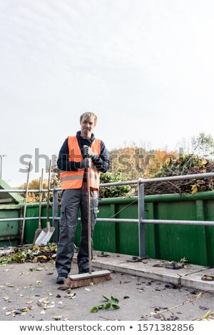 Man sweeping the floor of recycling center after delivering waste green Stock photo © Kzenon