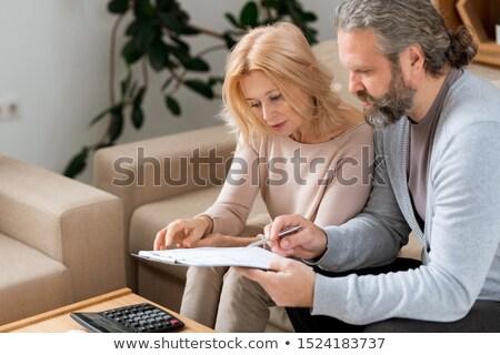Brodaty dojrzały mężczyzna wskazując umowy czytania żona Zdjęcia stock © pressmaster