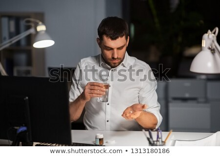 businessman taking medicine pills at night office stock photo © dolgachov