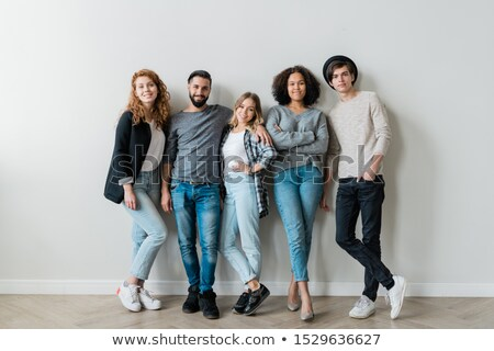 Happy intercultural guys and girls in casualwear standing against white wall Stock photo © pressmaster
