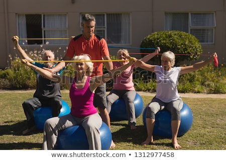 Front view of active senior man and woman exercising with elastic band and ball in park Stock photo © wavebreak_media