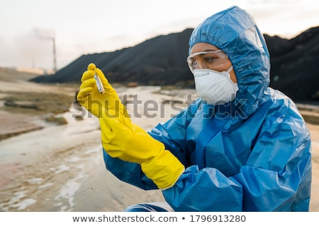 Young woman in mask, gloves and eyeglasses looking at blue substance in flask Stock photo © pressmaster
