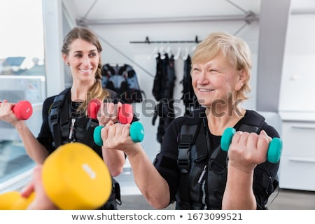 Group of people in wireless ems gym exercising with weight Stock photo © Kzenon