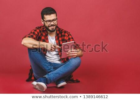 asian man sitting on floor using tablet stock photo © szefei