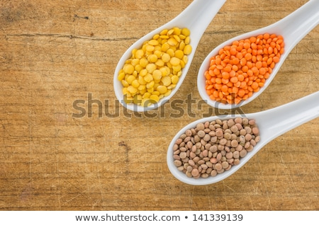 Different types of lentils on porcelain spoons Stock photo © Zerbor