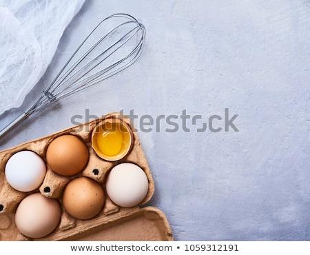 Raw eggs and whisk Stock photo © yelenayemchuk