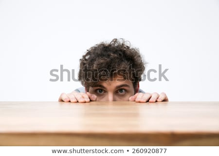 young man with curly hair peeking from behind the desk stock photo © deandrobot