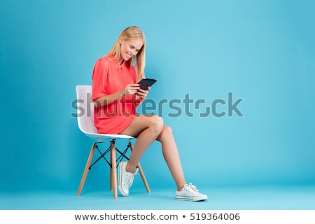pretty blond woman sitting on red chair stock photo © juniart