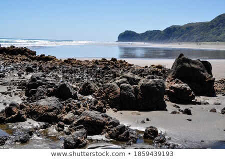 Black rock stone sand beach coast in front of blue sea with mountain background Stock photo © attiarndt