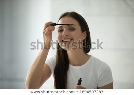 woman applying mascara on eyelashes stock photo © deandrobot