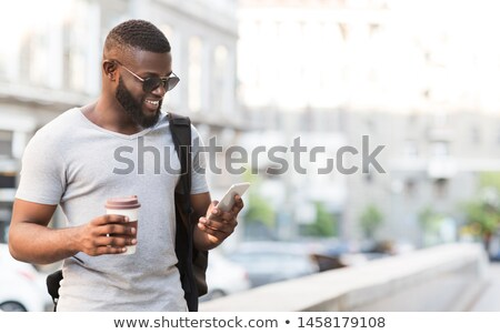 man with backpack walking and drinking coffee in the city stock photo © deandrobot