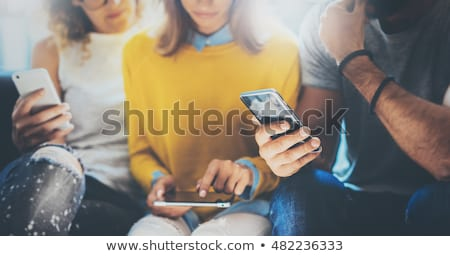 friends sitting in cafe woman touching phone stock photo © deandrobot