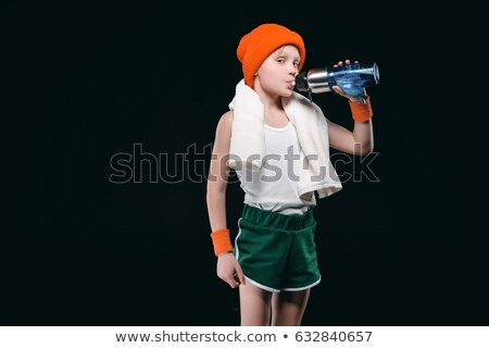Sporty boy drinking water from bottle and looking at camera isolated on black Stock photo © LightFieldStudios