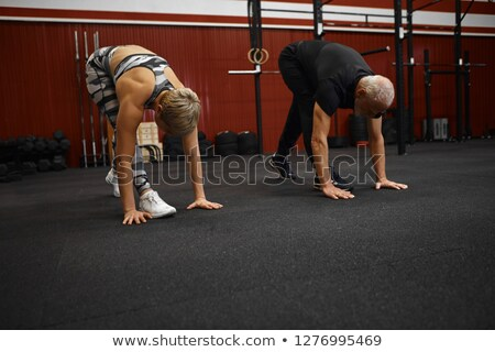 Happy trainer teaching senior people while exercising Stock photo © wavebreak_media