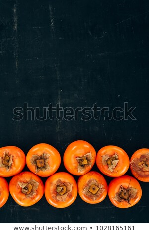 top view of rows of ripe yummy persimmons on black Stock photo © LightFieldStudios