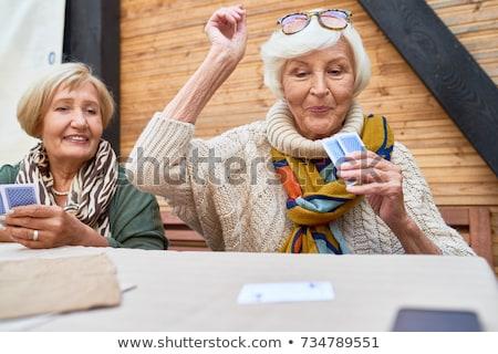 Kıdemli kadın iskambil kartları gülen Stok fotoğraf © IS2