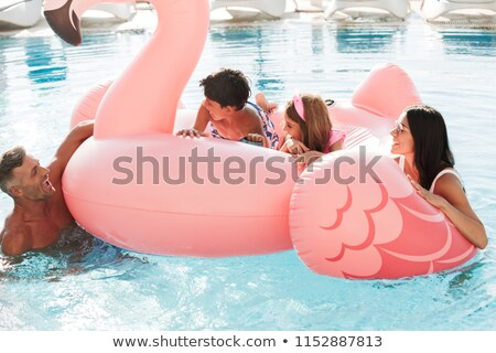 Portrait of beautiful joyous woman and man with kids swimming in Stock photo © deandrobot