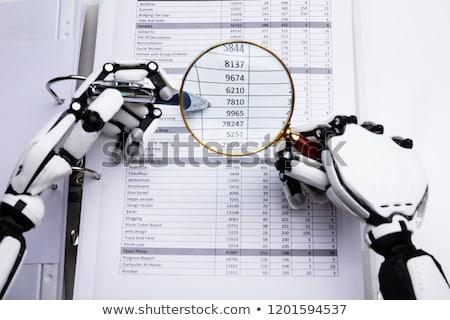 Robotic Hand Examining Financial Data Stock photo © AndreyPopov