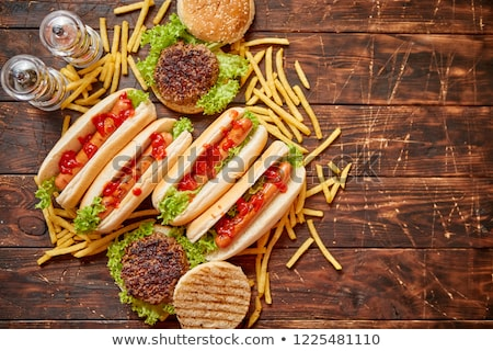 Fastfood assortment. Hamburgers and hot dogs placed on rusty wood table Stock photo © dash