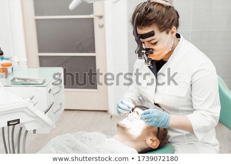 dentist treating patient teeth at dental clinic Stock photo © dolgachov