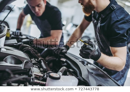 handsome mechanic job in uniform working on car stock photo © lopolo
