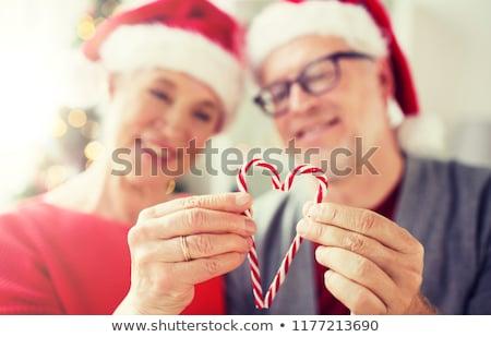 senior couple with heart of christmas candy canes stock photo © dolgachov