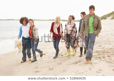 Group Of Young Friends Walking Along Autumn Shoreline Stock photo © monkey_business