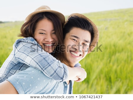 Millennial couple piggy back against blurry meadow Stock photo © wavebreak_media