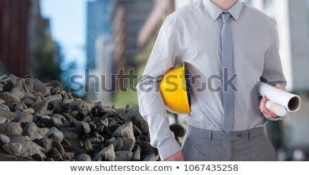 Rubble stones with Architect Construction worker holding helmet and blueprints in city Stock photo © wavebreak_media
