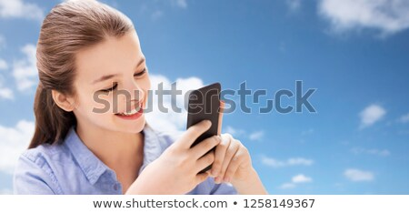 smiling girl messaging on smartphone over blue sky Stock photo © dolgachov