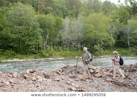 Two mature trippers with trekking sticks and backpacks moving along riverside Stock photo © pressmaster