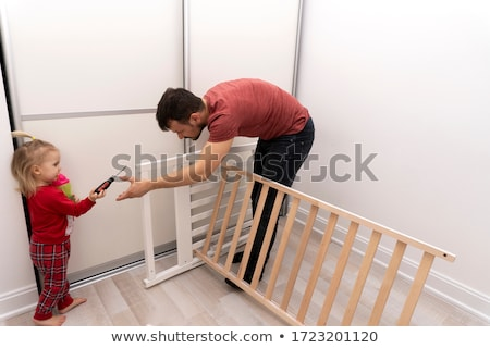 happy father with screwdriver assembling baby bed Stock photo © dolgachov
