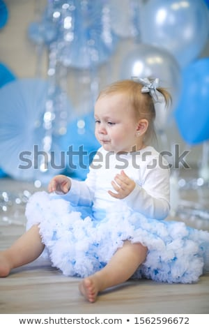 Stock photo: Cheerful children's birthday baby girl on a background of blue air-blasting and blue papyrus circles