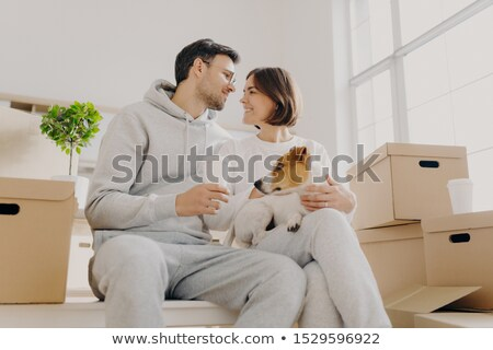 Indoor shot of affectionate woman and man express love to each other, have good relationship, drink  Stock photo © vkstudio