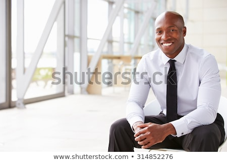 Image of young bald african american man smiling and looking at  Stock photo © deandrobot