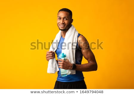Image of sportsman with towel over his neck drinking water after Stock photo © deandrobot