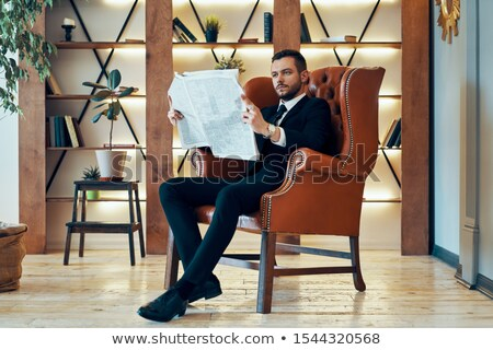 Confident young businessman reading newspaper and latest news while sitting in armchair Stock photo © GVS