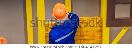 A boy plays in the builder in construction clothes and a helmet BANNER, LONG FORMAT Stock photo © galitskaya