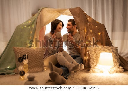 couple drinking coffee or tea in kids tent at home Stock photo © dolgachov
