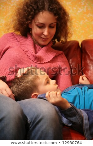Son lies on knees of mother seating on sofa
