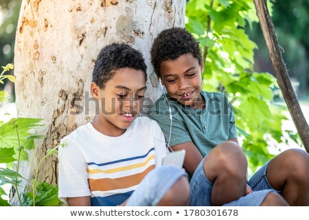Casual menino sessão portátil music player jovem Foto stock © lovleah