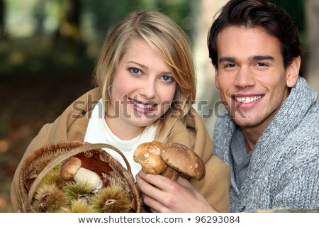 couple picking mushrooms and chestnuts in the forest stock photo © photography33