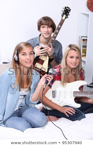 Three teenagers in bedroom with electric guitar Stock photo © photography33