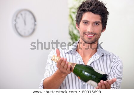 man offering a bottle of champagne at five minutes to midnight stock photo © photography33