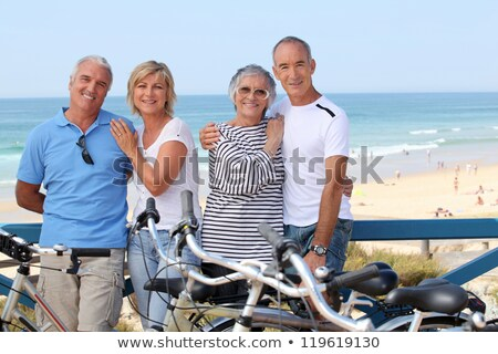 Foto stock: Senior Couple Riding Bikes By The Ocean
