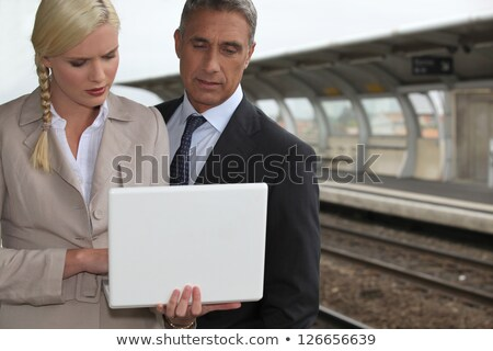 business couple with a laptop on a railway platform stock photo © photography33