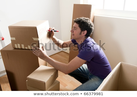Young man writing on moving boxes Stock photo © photography33