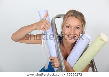 Stock photo: female diy enthusiast holding wallpaper rolls