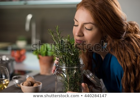 Woman smelling herbs in the kitchen Stock photo © photography33